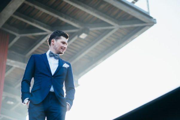 novio en traje azul con moño
