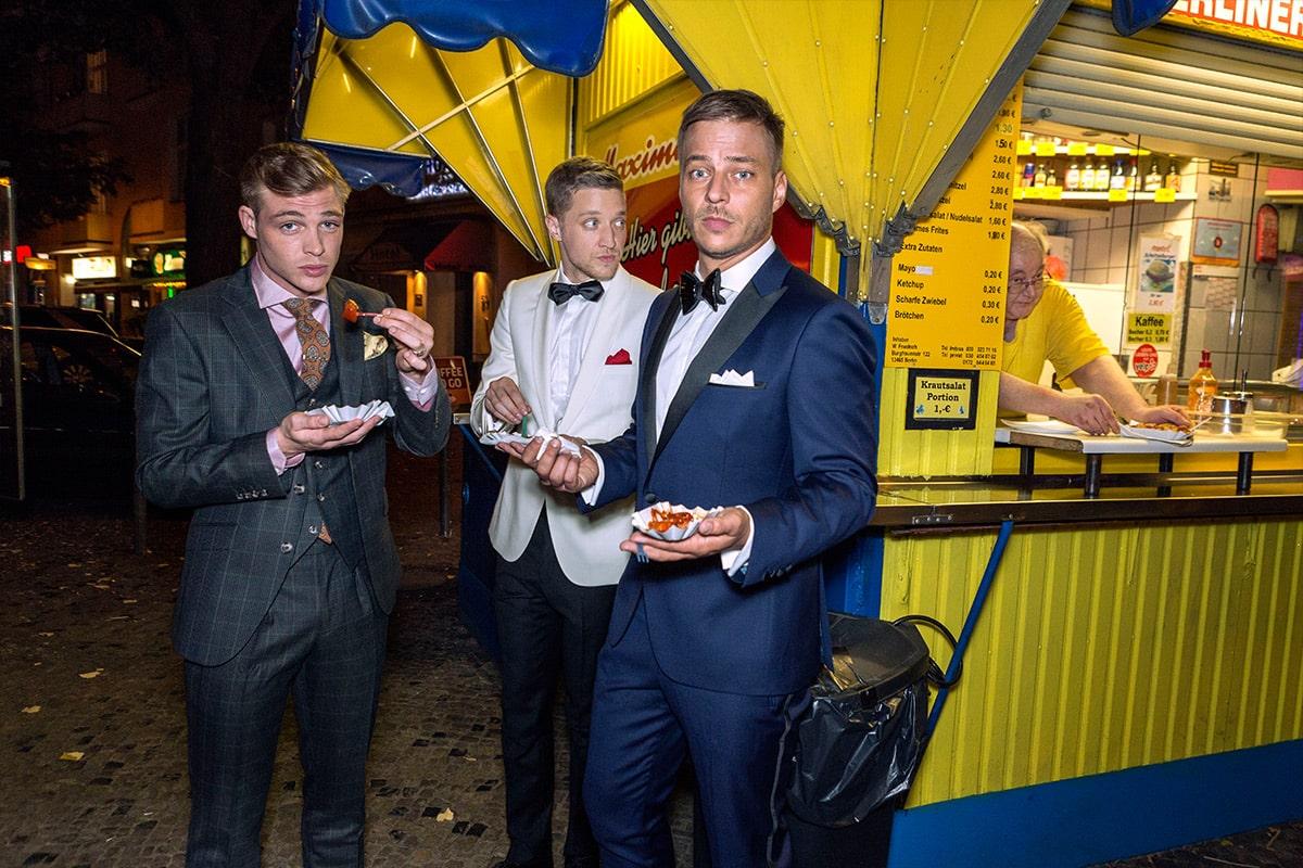 3 hombres en traje comiendo currywurst
