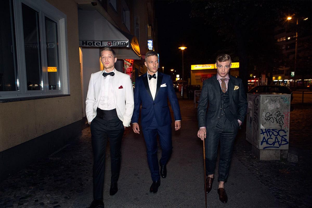 3 hombres en trajes elegantes caminado